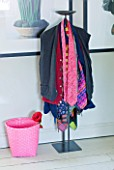 PAULA PRYKES HOUSE  SUFFOLK: CLOTHES STAND IN BEDROOM LAYERED WITH CLOTHES