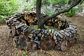 JACQUELINE MORABITO  FRANCE - HUGE LOGS PILED TOGETHER AS A CIRCULAR SCULPTURE