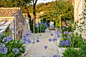 THE ROU ESTATE  CORFU  GREECE: DESIGNER: DOMINIC SKINNER - MEDITTERANEAN STYLE GARDEN - GRAVEL PATH AND AGAPANTHUS WITH THE WELL IN BACKGROUND