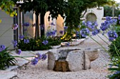 THE ROU ESTATE  CORFU  GREECE: DESIGNER: DOMINIC SKINNER - MEDITTERANEAN STYLE GARDEN - GRAVEL PATH AND AGAPANTHUS BESIDE THE WELL