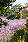 THE ROU ESTATE  CORFU  GREECE: DESIGNER: DOMINIC SKINNER - MEDITTERANEAN STYLE GARDEN - STONE STEPS SURROUNDED BY AGAPANTHUS AND TULBAGHIA VIOLACEA
