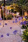 THE ROU ESTATE  CORFU  GREECE: DESIGNER: DOMINIC SKINNER - MEDITTERANEAN STYLE GARDEN - GRAVEL PATH  WELL AND AGAPANTHUS LIT UP AT NIGHT. LIGHTING