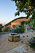 THE ROU ESTATE  CORFU  GREECE: DESIGNER: DOMINIC SKINNER - MEDITTERANEAN STYLE GARDEN - GRAVEL PATH  AGAPANTHUS AND THE WELL