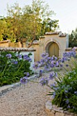 THE ROU ESTATE  CORFU  GREECE: DESIGNER: DOMINIC SKINNER - MEDITTERANEAN STYLE GARDEN - GRAVEL PATH AND AGAPANTHUS WITH GREEN DOOR IN BACKGROUND