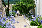 THE ROU ESTATE  CORFU  GREECE: DESIGNER: DOMINIC SKINNER - MEDITTERANEAN STYLE GARDEN - GRAVEL PATH AND AGAPANTHUS WITH WELL