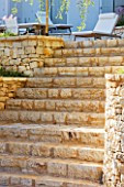 CORFU  GREECE: DESIGNER: DOMINIC SKINNER - STONE STEPS UP TO PATIO WITH SUN LOUNGERS