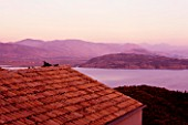 THE ROU ESTATE  CORFU  GREECE: DESIGNER: DOMINIC SKINNER - VIEW OVER HOUSE ROOF TO ALBANIAN MOUNTAINS AT DAWN