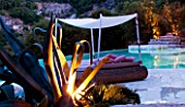 THE ROU ESTATE  CORFU  GREECE: DESIGNER: DOMINIC SKINNER -  A PLACE TO SIT - THE SWIMMING POOL  LIT UP AT NIGHT WITH LOUNGER SEAT AND CACTUS. LIGHTING