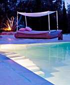 THE ROU ESTATE  CORFU  GREECE: DESIGNER: DOMINIC SKINNER -  A PLACE TO SIT - THE SWIMMING POOL AREA  LIT UP AT NIGHT WITH LUXURY BED AND CACTUS. LIGHTING