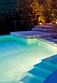 THE ROU ESTATE  CORFU  GREECE: DESIGNER: DOMINIC SKINNER - THE SWIMMING POOL AREA  LIT UP AT NIGHT WITH STEPS. LIGHTING