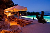 THE ROU ESTATE  CORFU  GREECE: DESIGNER: DOMINIC SKINNER - THE SWIMMING POOL AREA  LIT UP AT NIGHT WITH SUN LOUNGERS. LIGHTING