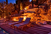 THE ROU ESTATE  CORFU  GREECE: DESIGNER: DOMINIC SKINNER - THE SWIMMING POOL AREA  LIT UP AT NIGHT WITH SUN LOUNGERS AND WATERFALL. LIGHTING