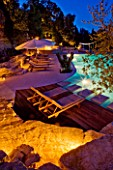 THE ROU ESTATE  CORFU  GREECE: DESIGNER: DOMINIC SKINNER - THE SWIMMING POOL AREA  LIT UP AT NIGHT - SUN LOUNGERS AND DECKING. LIGHTING