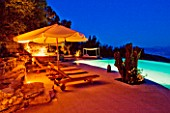 THE ROU ESTATE  CORFU  GREECE: DESIGNER: DOMINIC SKINNER - THE SWIMMING POOL AREA  LIT UP AT NIGHT - SUN LOUNGERS. LIGHTING