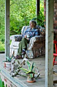 MOORS MEADOW GARDEN & NURSERY  HEREFORDSHIRE: ROS BISSELL SITTING ON AN ARMCHAIR ON HER VERANDA