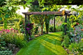 MEADOW FARM  WORCESTERSHIRE: CURVED LAWN AND PERGOLA IN SUMMER