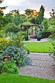 MEADOW FARM  WORCESTERSHIRE: GRAVEL STEPS TO CIRCULAR LAWN LEADING TO PERGOLA AND CONTAINER WITH AGAVE AMERICANA