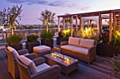 DESIGNER: CHARLOTTE ROWE  LONDON: ROOF GARDEN - A PLACE TO SIT - WICKER FURNITURE  WOODEN PERGOLA  CONTAINERS PLANTED WITH OLIVE TREES  PENNISETUM HAMELYN    PINUS MUGO. LIGHTING,  DECKS, DECKING, SCREENING