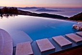 THE ROU ESTATE  CORFU - DESIGNER DOMINIC SKINNER - THE SWIMMING POOL AT DAWN WITH VIEWS OF THE ALBANIAN MOUNTAINS IN THE BACKGROUND
