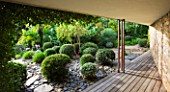 DESIGNER: JEAN-LAURENT FELIZIA  FRANCE: WOODEN FLOOR BESIDE SLATE AREA PLANTED WITH TOPIARY BALLS