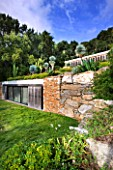 DESIGNER: JEAN-LAURENT FELIZIA  FRANCE: POOL HOUSE WITH LAWN AND SUCCULENTS GROWING ON THE ROOF