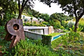 DESIGNER: JEAN-LAURENT FELIZIA  FRANCE: POOL HOUSE WITH LAWN  SWIMMING POOL AND SUCCULENTS GROWING ON THE ROOF. METAL SCULPTURE IN FOREGROUND