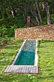 DESIGNER: JEAN-LAURENT FELIZIA  FRANCE: LAWN WITH SWIMMING POOL AND WALL WITH WOODLAND BEHIND