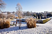 PETTIFERS  OXFORDSHIRE: GARDEN IN SNOW IN WINTER - VIEW TOWARDS THE PARTERRE WITH CLIPPED TOPIARY SHAPES AND THE COUNTRYSIDE BEYOND