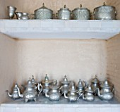 DESIGNERS ERIC OSSART AND ARNAUD MAURIERES  MOROCCO: AL HOSSOUN - SHELVES IN LIVING ROOM WITH TEAPOTS