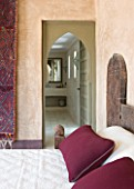 DESIGNERS ERIC OSSART AND ARNAUD MAURIERES  MOROCCO: AL HOSSOUN - BEDROOM WITH WOODN BED  MAGENTA CUSHIONS AND CARPET ON WALL - VIEW THROUGH DOORWAY TO SHOWER ROOM