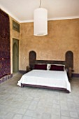 DESIGNERS ERIC OSSART AND ARNAUD MAURIERES  MOROCCO: AL HOSSOUN - BEDROOM WITH WOODN BED  MAGENTA CUSHIONS AND CARPET ON WALL