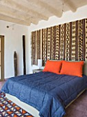 DESIGNERS ERIC OSSART AND ARNAUD MAURIERES  MOROCCO: AL HOSSOUN - BEDROOM WITH BLUE COVER AND PINK PILLOWS - CARPET ON WALL
