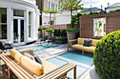 ROOF GARDEN AT GROUND LEVEL BY STEPHEN WOODHAMS, LONDON: TERRACE/SEATING AREA WITH WOODEN BENCHES, BOX BALLS IN CONTAINERS, DECKING WITH FROSTED GLASS SKYLIGHTS, SCREEN, MIRROR, DECKS, DECKING, DECKED