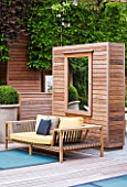 MODERN ROOF GARDEN BY STEPHEN WOODHAMS, LONDON: CEDARWOOD SCREEN AND MIRROR WITH WOODEN BENCH/SEAT. DECK AND FROSTED GLASS SKYLIGHTS TO POOL BELOW. PLEACHED HORNBEAMS. CONTEMPORARY, DECKS, DECKING, DECKED