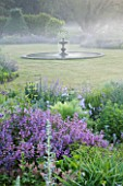 NARBOROUGH HALL GARDENS  NORFOLK: DAWN LIGHT ON THE FOUNTAIN IN THE LAWN WITH BLUE BORDERS AROUND