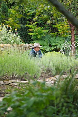 SANDHILL_FARM_HOUSE__HAMPSHIRE__DESIGNER_ROSEMARY_ALEXANDER__GARDENER_WITH_HAT_CLIPPING_BOX_BALLS_IN