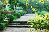 SANDHILL FARM HOUSE  HAMPSHIRE - DESIGNER ROSEMARY ALEXANDER - WIDE GRAVEL PATH EDGED WITH CLIPPED BOX LEADING TO A METAL SEAT IN THE FRONT GARDEN