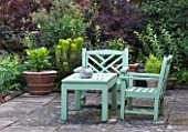 SANDHILL FARM HOUSE  HAMPSHIRE - DESIGNER ROSEMARY ALEXANDER - GREEN PAINTED WOODEN BENCH AND CHAIRS ON PATIO