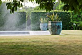 PRIVATE GARDEN, COTSWOLDS: DESIGNER ALISON HENRY - LAWN, SWIMMING POOL, BRONZE CONTAINERS WITH CORDYLINE. FORMAL, WATER, CLASSIC,  ENGLISH,  GARDEN