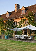 DESIGNER ALISON HENRY, PRIVATE GARDEN, COTSWOLDS - THE HOUSE WITH LAWN, STONE TERRACE / PATIO WITH SEATS AND CANVAS SAIL CANOPY - COUNTRY, GARDEN, SUMMER, CLASSIC, ENGLISH