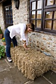 DESIGNER CLARE MATTHEWS - GROWING STRAWBERRIES AND NASTURTIUMS IN A STRAW BALE: USE A BREAD KNIFE TO CREATE A HOLE FOR PLANTING
