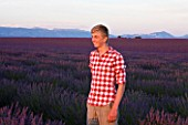 TEENAGE BOY (AGED 16) WITH RED AND WHITE SHIRT IN FIELD OF PURPLE LAVENDER NEAR VALENSOLE  PROVENCE  FRANCE. SUMMER  JULY
