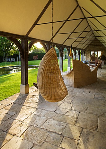 WHATLEY_MANOR__WILTSHIRE_SWING_SEAT_CHAIR_IN_THE_COTSWOLD_STONE_LOGGIA_BUILDING_WITH_LAWN__POOL_AND_