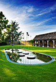 WHATLEY MANOR  WILTSHIRE: THE LOGGIA GARDEN WITH COTSWOLD STONE LOGGIA BUILDING  LAWN  POOL AND WATER FEATURE BY SIMON ALLISON