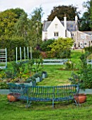 DESIGNER CLARE MATTHEWS: THE FRUIT AND VEGETABLE GARDEN IN DEVON. RAISED  BLUE PAINTED WOODEN BEDS AND ELEGANT CURVED BLUE METAL BENCH WITH THE HOUSE BEHIND