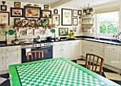 DESIGNER BUTTER WAKEFIELD  LONDON - THE KITCHEN WITH BOTANICAL PRINTS AND TABLE OF GREEN AND WHITE SQUARES MADE BY BUTTERS MOTHER-IN-LAW - FELICITY WAKEFIELD