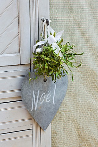 DESIGNER_JACKY_HOBBS__LONDON_DINING_ROOM_AT_CHRISTMAS__SLATE_NOEL_HEART_WITH_WHITE_RIBBON_AND_MISTLE