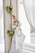 DESIGNER: JACKY HOBBS  LONDON: BEDROOM AT CHRISTMAS WITH HOLLY DECORATION TIED TO MIRROR FRONTED WARDROBE