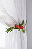 DESIGNER: JACKY HOBBS  LONDON: BEDROOM AT CHRISTMAS WITH HOLLY DECORATION TIED TO CURTAIN