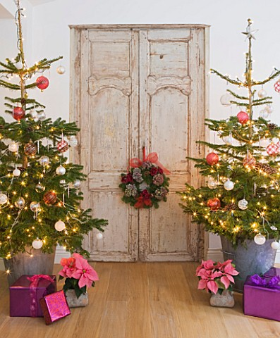 DESIGNER_JACKY_HOBBS__LONDON_THE_LIVING_ROOM_AT_CHRISTMAS_WITH_DOOR__WREATH_AND_TWO_CHRISTMAS_TREES_